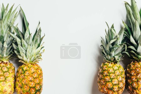 top view of fresh ripe pineapples on white background