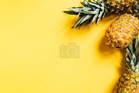 Photo for Top view of fresh ripe pineapples on yellow background - Royalty Free Image