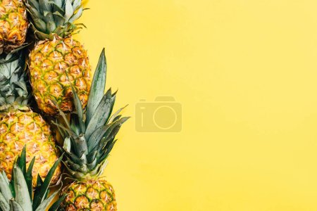 Photo for Top view of fresh tasty pineapples on yellow background - Royalty Free Image