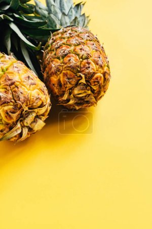 fresh ripe pineapples on yellow background with copy space