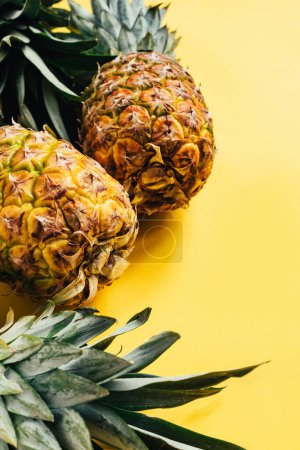 selective focus of fresh ripe pineapples with green leaves on yellow background