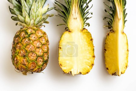 Photo for Flat lay with cut and whole ripe pineapples with green leaves on white background - Royalty Free Image
