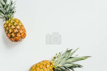 top view of fresh ripe pineapples with green leaves on white background