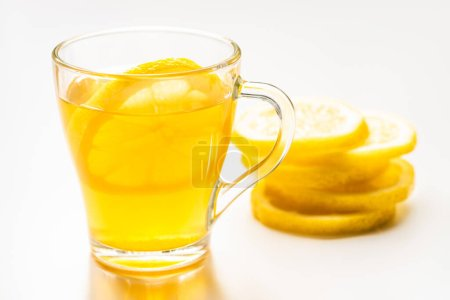selective focus of of hot tea in glass near lemon slices on white background