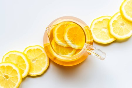 top view of hot tea with lemon slices on white background