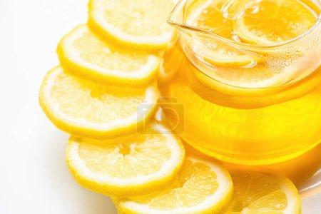 Photo pour Vue rapprochée du thé chaud dans une théière en verre avec des tranches de citron sur fond blanc - image libre de droit
