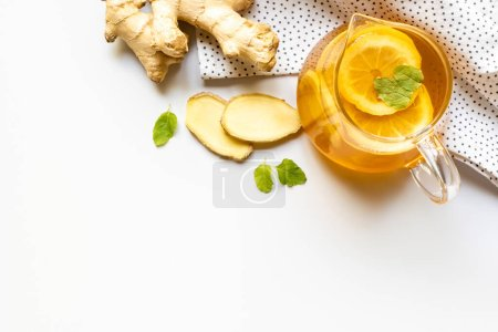 Photo for Top view of hot tea on napkin near ginger root, lemon and mint on white background - Royalty Free Image