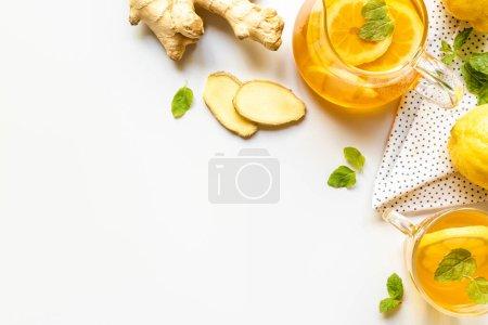 Photo pour Vue du dessus du thé chaud sur serviette près de la racine de gingembre, citron et menthe sur fond blanc - image libre de droit