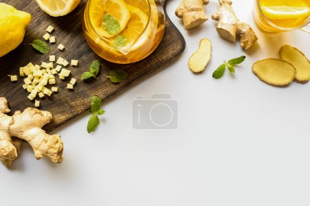 Photo for Top view of hot tea near ginger root, lemon and mint on wooden cutting board on white background - Royalty Free Image