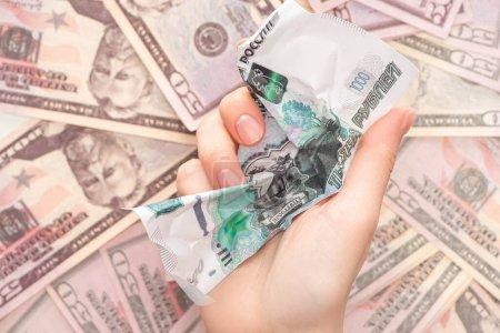 Photo pour Vue du dessus de la femme tenant le billet de banque rouble froissé près de dollars - image libre de droit