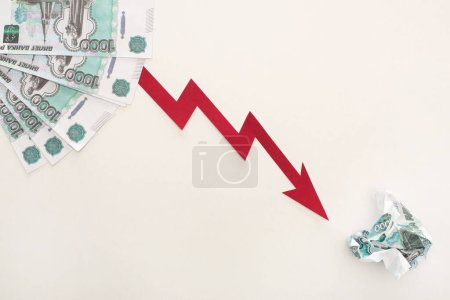 top view of crisis graph near ruble banknotes isolated on white