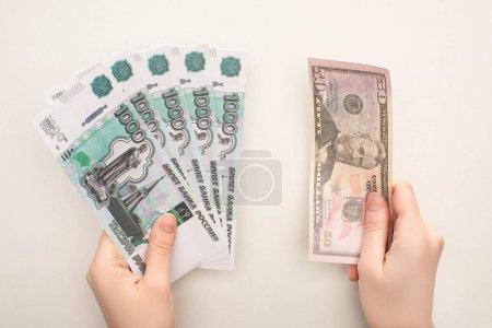 Photo pour KYIV, UKRAINE - 25 MARS 2020 : vue de dessus de la femme tenant des roubles russes et un billet en dollar isolé sur blanc - image libre de droit