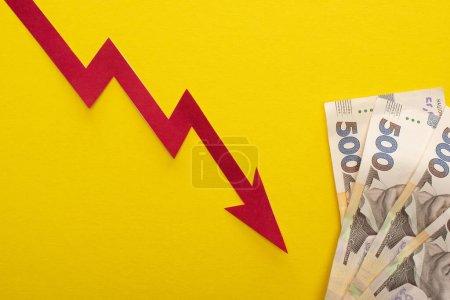 Photo pour Vue du haut du graphique de crise près des billets de banque en hryvnia ukrainienne isolés sur jaune - image libre de droit