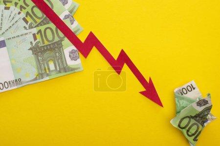 Photo pour KYIV, UKRAINE - 25 MARS 2020 : vue du haut du graphique de crise et des billets en euros isolés sur jaune - image libre de droit