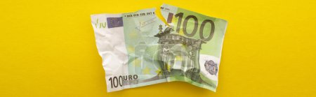 KYIV, UKRAINE - MARCH 25, 2020: panoramic orientation of crumpled euro banknote isolated on yellow