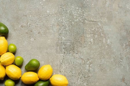 Photo for Top view of colorful limes, avocado and lemons on grey concrete surface - Royalty Free Image
