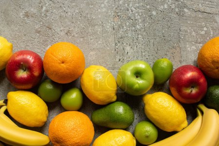 Photo for Top view of tasty colorful fruits on grey concrete surface - Royalty Free Image