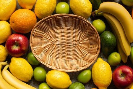 Photo pour Vue de dessus des fruits colorés savoureux autour du panier en osier - image libre de droit