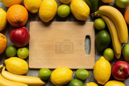 Photo for Top view of tasty colorful fruits and wooden cutting board - Royalty Free Image