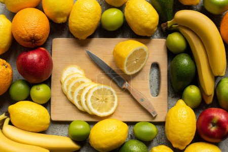 top view of tasty colorful fruits and wooden cutting board with lemon slices and knife