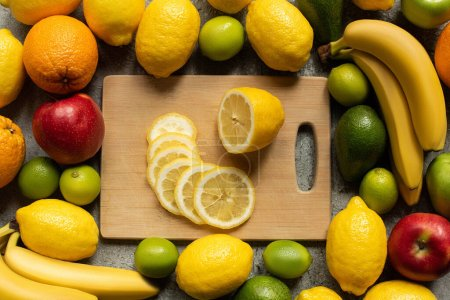 Photo for Top view of tasty colorful fruits and wooden cutting board with lemon slices - Royalty Free Image