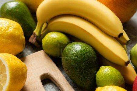 Photo pour Vue rapprochée de fruits colorés savoureux et planche à découper en bois - image libre de droit