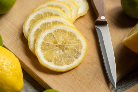Photo for Close up view of sliced lemon on wooden cutting board with knife - Royalty Free Image