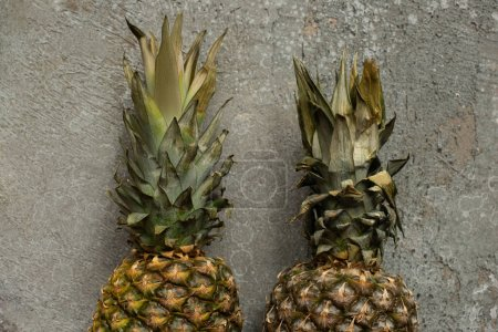 Photo for Top view of ripe pineapples on grey concrete surface - Royalty Free Image