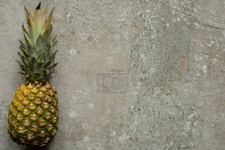 Photo for Top view of ripe pineapple on grey concrete surface with copy space - Royalty Free Image