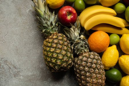 Photo for Top view of colorful fresh fruits on grey concrete surface - Royalty Free Image
