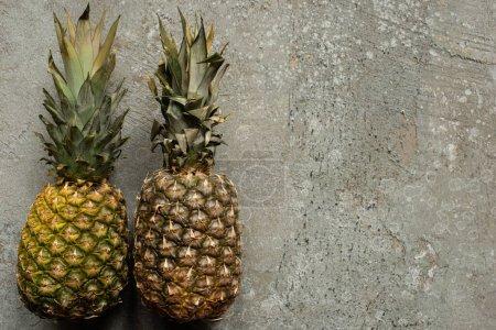 Ansicht von reifen Ananas auf grauer Betonoberfläche mit Kopierraum
