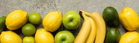 Photo for Top view of colorful avocado, limes and lemons on grey concrete surface, panoramic shot - Royalty Free Image
