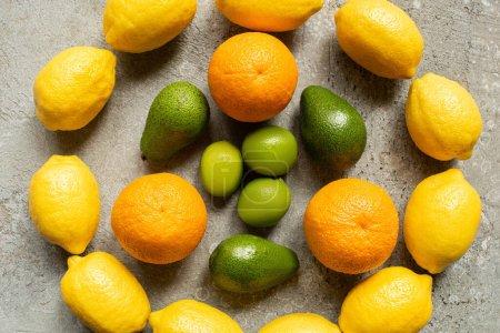 Photo pour Vue de dessus des oranges colorées, avocat, chaux et citrons disposés en cercle sur la surface en béton gris - image libre de droit