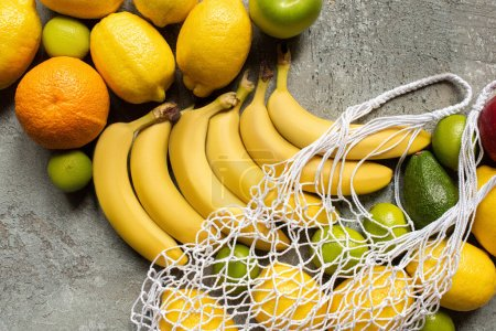 Photo for Top view of colorful delicious fruits and string bag on grey concrete surface - Royalty Free Image