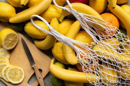 Photo pour Vue de dessus des fruits colorés, planche à découper avec couteau et citron tranché, sac à ficelle sur la surface en béton gris - image libre de droit