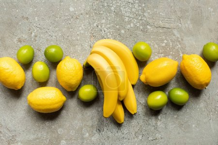 top view of colorful bananas, limes and lemons on grey concrete surface
