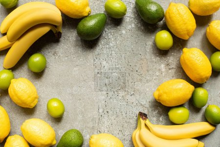 Photo for Top view of colorful bananas, avocado, limes and lemons on grey concrete surface with copy space - Royalty Free Image