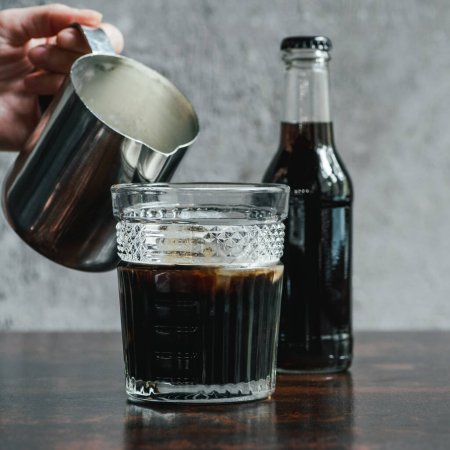 cropped view of woman pouring milk in cold brew coffee in glass near bottle on wooden table