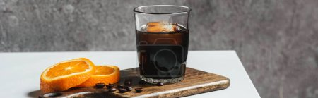 cold brew coffee with ice in glass near orange slices on chopping board and coffee beans on white table, panoramic shot