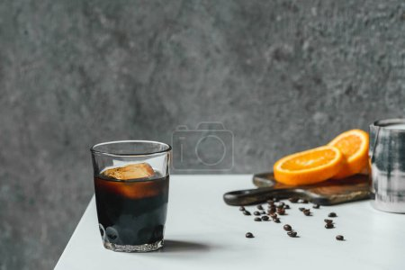 selective focus of cold brew coffee with ice in glass near orange slices on chopping board and coffee beans on white table