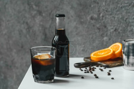 selective focus of cold brew coffee with ice in glass and bottle near orange slices on chopping board and coffee beans on white table
