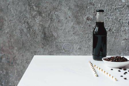 Selektiver Fokus von kaltem Brühkaffee mit Eis in der Flasche in der Nähe von Trinkhalmen und Kaffeebohnen auf weißem Tisch