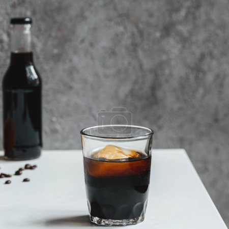selective focus of cold brew coffee with ice in glass on white table