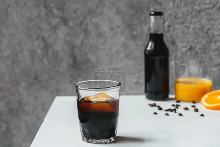 Photo pour Foyer sélectif de café infusé froid avec de la glace dans le verre et la bouteille près du jus d'orange et des grains de café sur la table blanche - image libre de droit