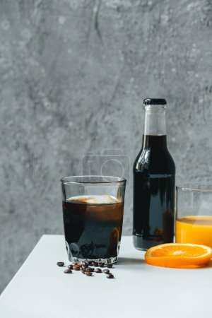 cold brew coffee with ice in glass and bottle near orange juice and coffee beans on white table