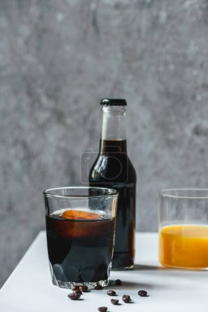 Photo for Selective focus of cold brew coffee with ice in glass and bottle near orange juice and coffee beans on white table - Royalty Free Image