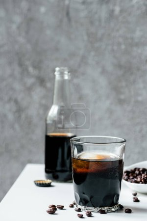 Photo for Selective focus of cold brew coffee with ice in glass near bottle and coffee beans on white table - Royalty Free Image