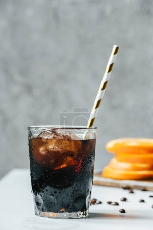 selective focus of cold brew coffee with ice and drinking straw on white table