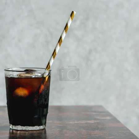 Photo for Cold brew coffee with ice and drinking straw in glass on wooden table - Royalty Free Image