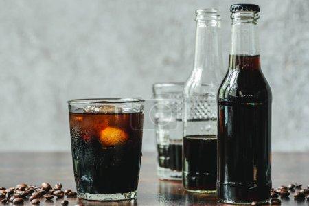 Photo pour Foyer sélectif de café infusé à froid avec de la glace dans le verre et les bouteilles près des grains de café - image libre de droit